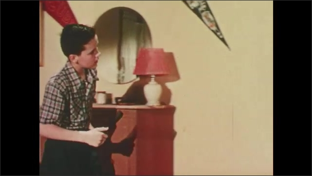1950s: Children sit. Boy brushes hair. Boy cleans face