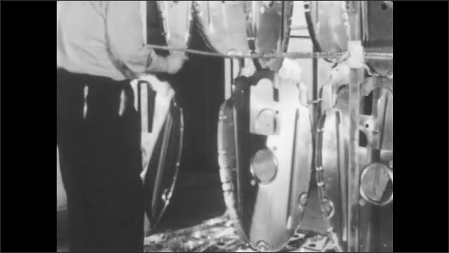 1940s: Worker attaches aluminum parts to metal rack. Man ties parts to arms of metal rack. Man consults graph meters on furnace unit.