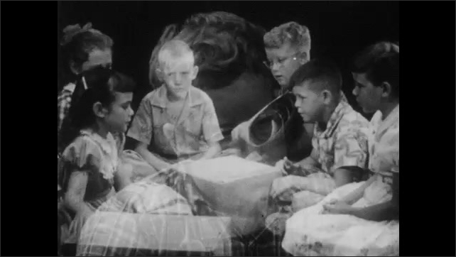 1950s:  three girls and two boys kneel around a large sheet of paper with boxes, talk and go silent. boy sits with children, waves arms and rejects cardboard houses.