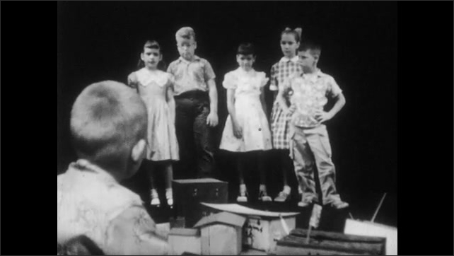 1950s: boys and girls walk away and argue as boy with buzz-cut sits near paper with cardboard models talks on dark studio set.