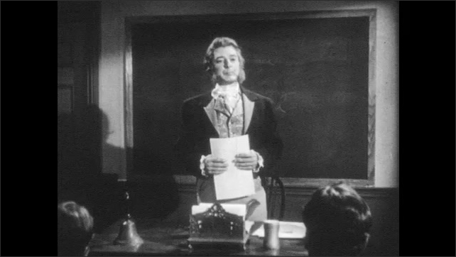 1940s: Longfellow stands in front of classroom and blackboard talking to students. The students rise and exit the classroom.