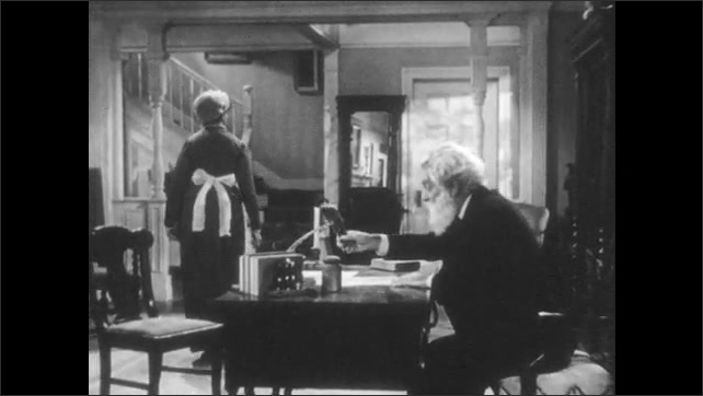 1940s: Man sits at desk, talks with housemaid. Woman walks away, man gets up from desk. Four children walk into room, carry chair, set chair down by desk.
