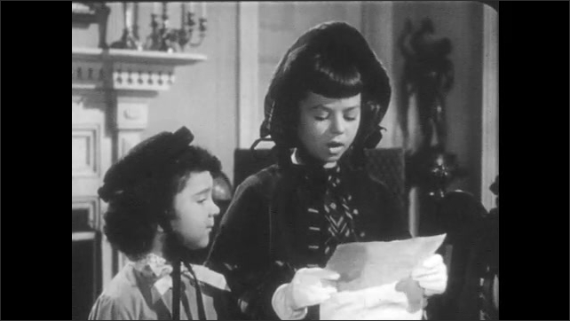1940s: Old man talks to children. Girl reads from paper.