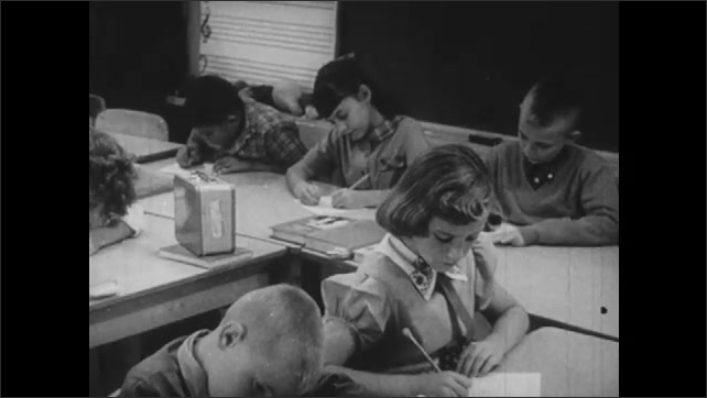 1960s: UNITED STATES: lady and girl at home. Girl works in class. Teacher puts up paper on wall. Teacher in class.