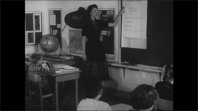 1960s: UNITED STATES: teacher talks to students in classroom. Teacher points to writing on board. Check your writing title. Student checks work