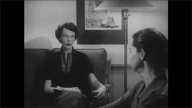 1960s: UNITED STATES: ladies talk in office. Teacher talks to school social worker. Lady sits in chair.