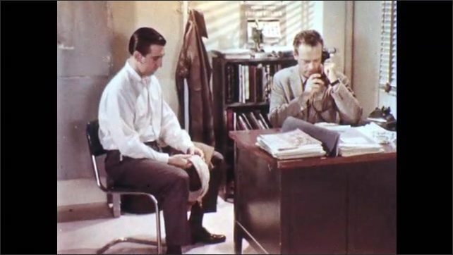 1950s: Men sit at desk and talk. Foreman pauses and answers phone. Foreman speaks into phone. Foreman hangs up phone and speaks to man at desk.