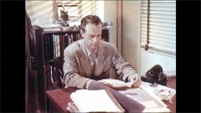 1950s: Worker walks from desk to door. Foreman sits and desk and speaks. Foreman shuffles through papers and thinks to self. Worker dons coat.