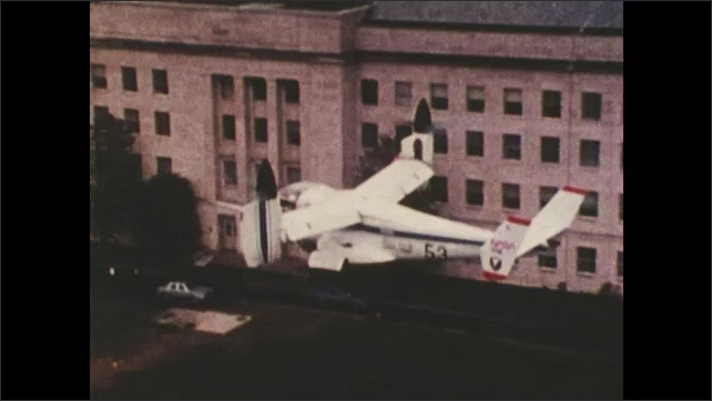 1970s: UNITED STATES: helicopter plane flies over buildings. Plane flies over mountains