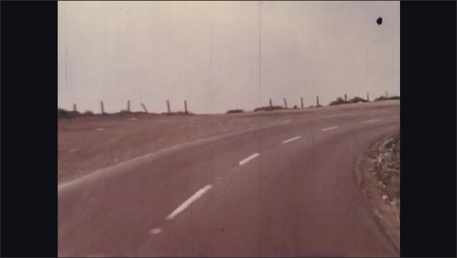 1960s: Car drives, child grabs ball from street, woman screams, car swerves around child. Woman with hands on her face looks relieved. Car drives on curvy mountain road.