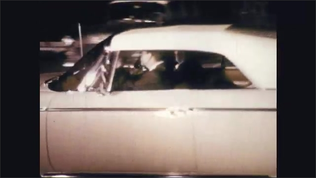 1960s: Two men drink. Man smokes cigarette. Man drives car off the parking lot at night. Man sits behind wheel at night, drives.