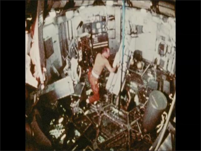 1970s: Astronaut moves equipment around module. Astronaut runs around module.