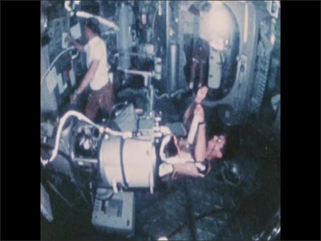 1970s: Man lays inside machine. Man adjusts straps and equipment on man and machine.