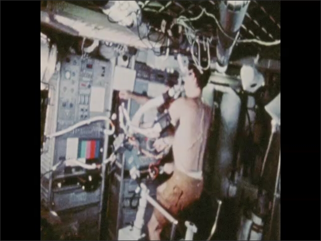 1970s: Man with tubes and wires on his body rides a stationary bike inside a spacecraft. Man adjusts controls near bicycle.