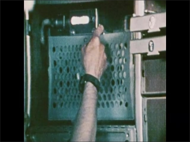 1970s: Man places small metal container onto vertical surface, secures container. Man presses buttons, surface shakes back and forth. Man removes container.