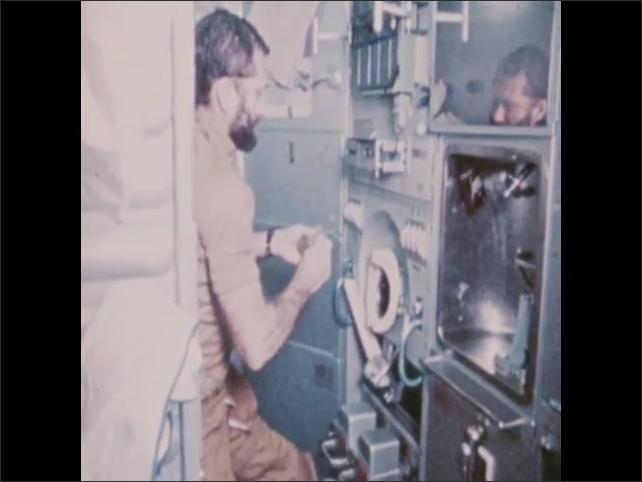 1970s: Man adjusts equipment on spacecraft, removes small object from compartment.