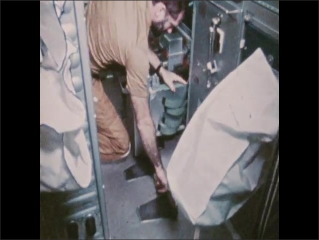 1970s: Man replaces containment bag in spacecraft restroom.