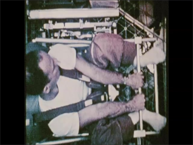 1970s: Man straps himself into chair scale, turns knob, weighs himself. Intertitle card.