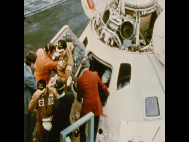 1970s: Astronauts exit command module aboard ship.