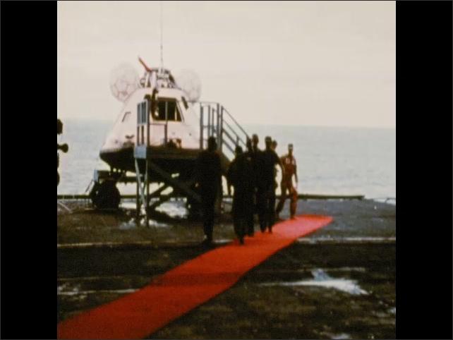 1970s: Astronauts exit command module aboard ship, walk down red carpet. Intertitle card.