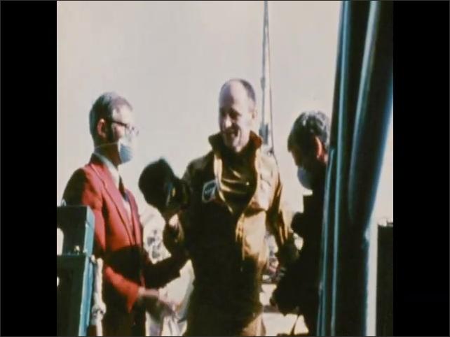1970s: Astronauts exit command module aboard ship, man sits down.