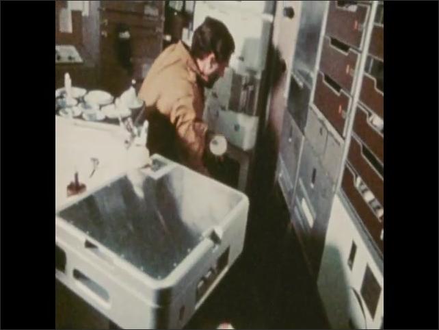 1970s: Man spins around in chair. Man draws blood from other man. Astronauts work on spacecraft.