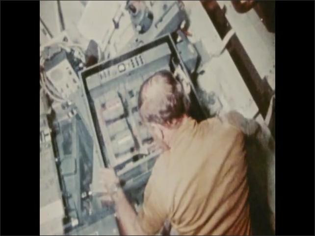 1970s: Astronauts work on board spacecraft.