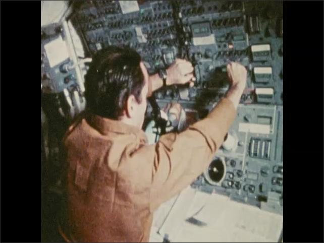 1970s: Men runs and flip around dome inside spacecraft. Man moves through spacecraft, adjusts dials. Man performs work outside spacecraft. Spacecraft in orbit above earth.
