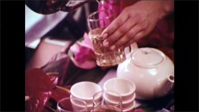 1970s: Airplane.  Stewardesses roll dessert tray down aisle.  Woman talks to passenger.  Woman pours coffee.