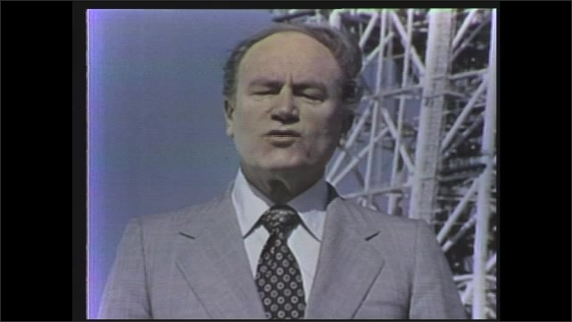 1970s: man talking in front of rocket launchpad