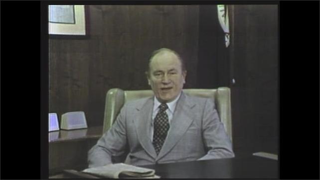 1970s: man sitting behind desk talking
