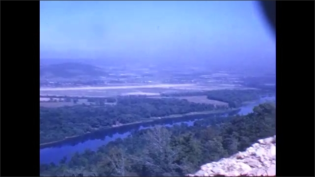 1940s: View from top of mountain. Group of people look across overlook at top of mountain. Man walks through field.