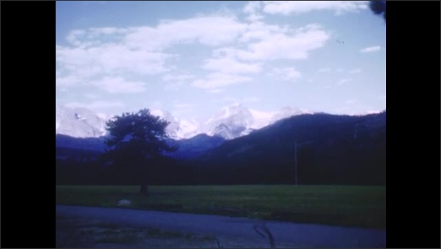 1940s: Scenic views of the Rocky mountains, pine trees, and a river with a road running next to it.