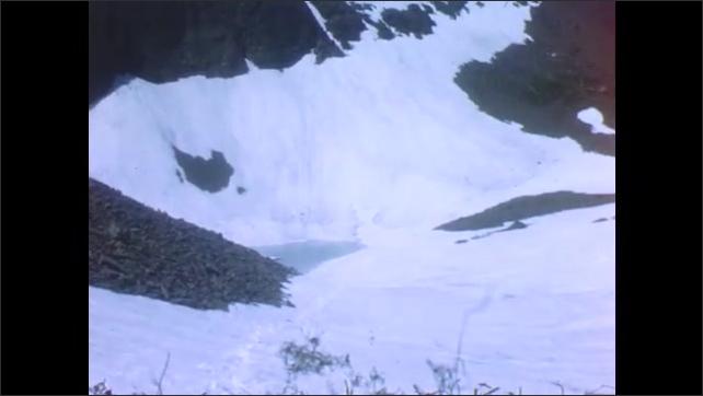 1940s: Man and woman climb slope. Snowy mountain lake. Small lake with iceberg.