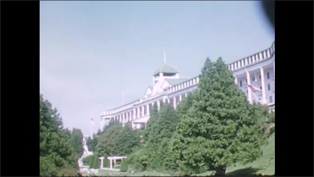 1940s: Large white building with several American flags on sunny day. Man woman and child in nineteenth century clothing.