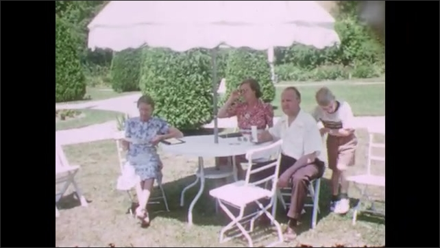 1940s: Large white house with columns. Family sitting under umbrella in field. Young boy stands up and waves, walking around table. Trees at edge of waterfront. Memorial with flag.