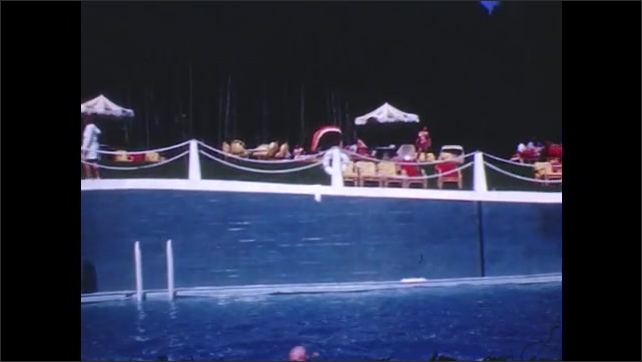 1940s: Diver jumps on board at pool. Crowd at pool in front of large white house. Boy jumps in pool and begins to swim.