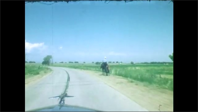 1940s: Driving down rural road. Cattle crossing street. More driving down rural road.