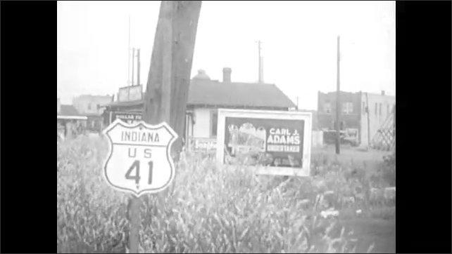 1930s: Girl sits in front of window, cutting paper with scissors. Girl in front of mirror. Road sign, Indiana US 41. Girl walks by Shell Station sign.