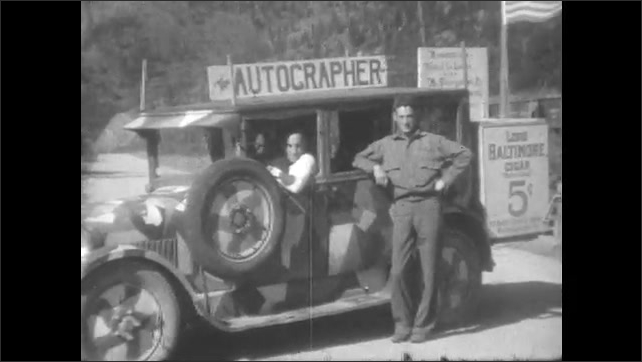 1930s: truck covered in camouflage paint drives past pine trees, stops on road so man poses next to signs for Lord Baltimore Cigars and The Autographer on van and driver.