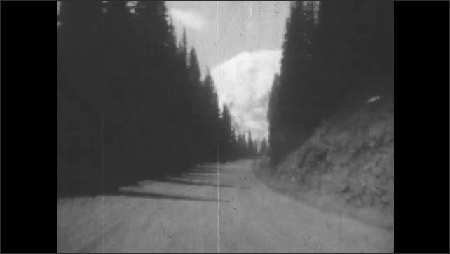 1930s:  dirt road winds uphill through pine tree forest to mountain with snowy peaks and stops in Montana national park. telephone poles run along highway on prairie.