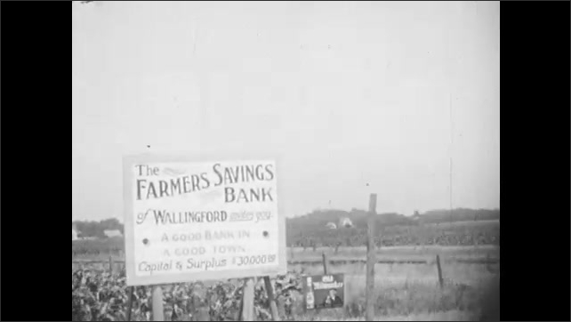 1930s: Cars driving down rural roads. Signs on side of road for service station and bank. Rural, country road. Woman and girl sit in parked car.
