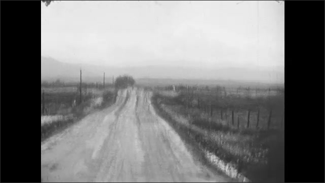 1930s: Dirt road through countryside, mountains. Man walks down road.