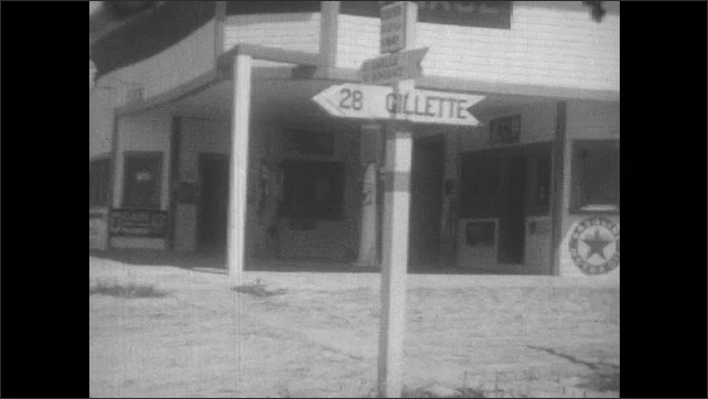 1930s: Car drives down dirt road into small village. Road sign for Gillette. Road sign for US 16 in field. Drive down dirt road, people on horseback.