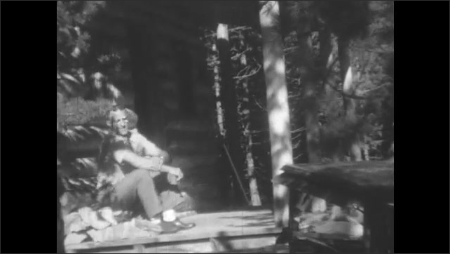 1930s: Man walks out of log cabin, sits down, stands up, leans against pole. Girl walks out of log cabin, stands by man. Man poses girl.