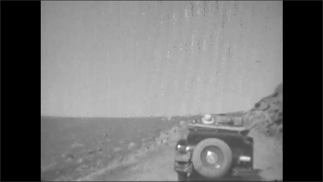 1930s: Convertible car drives along mountain road. Road sign for Wyoming US route 16. Car drives down dirt road.