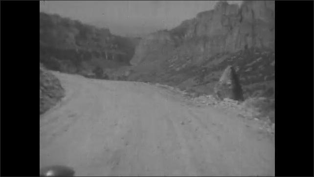 1930s: Car drives down dirt road through mountains. Winding road through canyon.