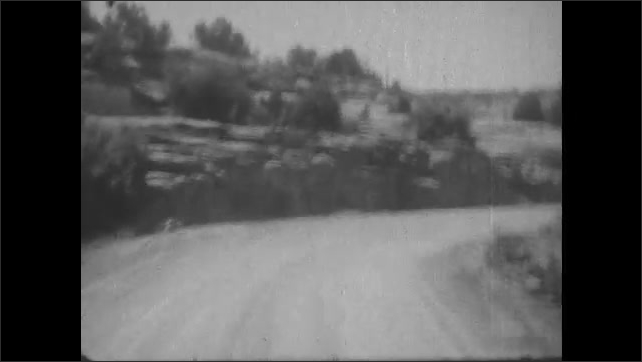 1930s: Car drives down winding mountain road. Man stands in desert.