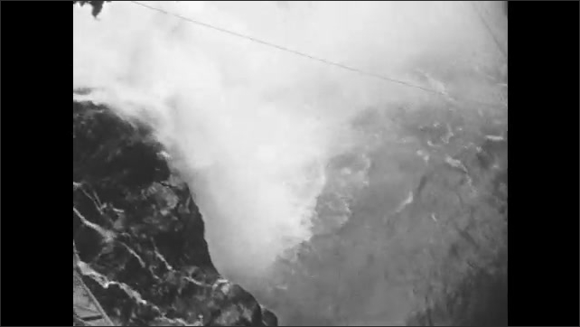 1930s: People walk along top of dam. Woman and girl stand at top of dam, look out over water. River flows under dam, through mountains.