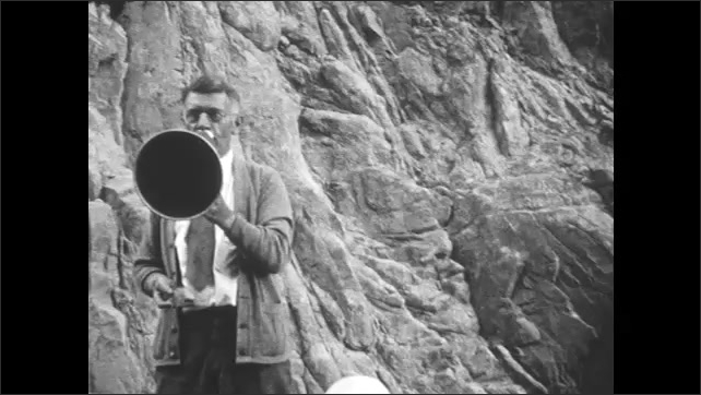 1930s: Water rushes down river, through mountains. People walk along top of dam. Man talks into megaphone. People walk up stairs. Waterfall.